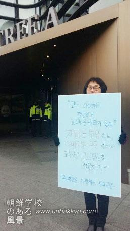 掲げたボードには「すべての子供たちは等しく教育を受ける権利があります。在日同胞を弾圧する安部政府を糾弾する」「朝鮮学校高校無償化適用せよ」と記されている。